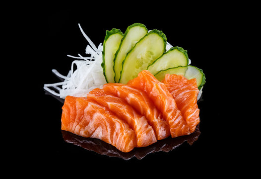Salmon sashimi over black background