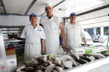Fish vendors pose for a picture while working in a street market in downtown Montevideo