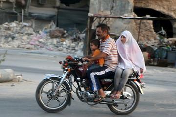 Residents drive a motorcycle near damaged buildings in Old Aleppo's Kadi Askar area, Syria