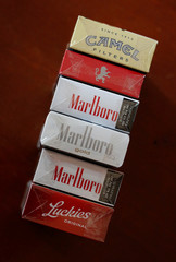 An illustration picture shows packs of Marlboro cigarettes, a pack of Camel cigarettes, and a pack of Lucky Strike cigarettes in a bar in Mexico City