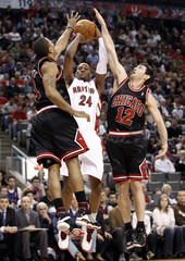 Raptors' Weems shoots between Bulls' Rose and Hinrich during the first half of their NBA basketball game in Toronto