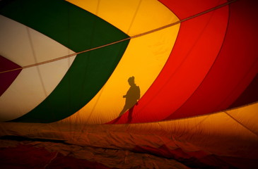 A woman's shadow is cast on the inside of a hot air balloon as it is inflated at sunrise on day one of the 2015 New Jersey Festival of Ballooning in Readington
