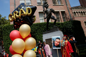 Balloons stand as graduates take pictures after a commencement ceremony at the University of Southern California (USC) in Los Angeles, California