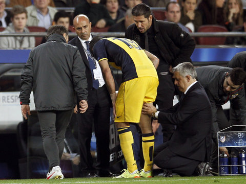 Atletico Madrid's Costa is checked by his team's doctor after injuring his right leg during their Champions League quarter-final first leg soccer match against Barcelona in Barcelona