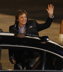 Singer McCartney greets after his arrival at the Silvio Pettirossi International Airport in Luque