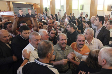 Residents take part in a funeral for victims killed in an attack on the Our Lady of Salvation church, in Baghdad