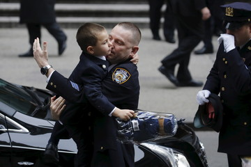 Ryan Lemm holds a stuffed bear as he is carried by a New York Police Department officer following the funeral of his father, NYPD officer Joseph Lemm, who was killed on duty in Afghanistan, in the Manhattan borough of New York