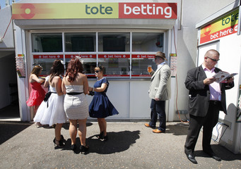 Racegoers stand outside a Tote betting window at Epsom Racecourse in southern England