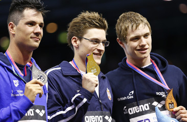 Serbia's gold medalist Stjepanovic is flanked by Italian silver medalist Mitchell D'Arrigo and Britain's bronze medalist Lelliott after the men's 400m Freestyle event at the European Swimming Championships in Berlin
