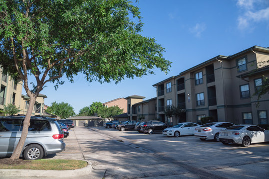 Typical apartment complex building in suburban area at Humble, Texas, US. Parked cars on uncovered parking lot along apartment blocks.