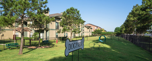 Community on-site dog park at the grassy backyard of a typical apartment complex building in suburban area at Humble, Texas, US. Off-leash dog park with pet stations, toys and bag dispensers