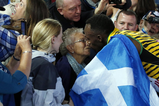Jamaica's Bolt kisses a woman in the stands after Jamaica won the men's 4x100m relay final at the 2014 Commonwealth Games in Glasgow