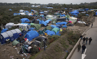"""Migrants walk past tents in the """"New Jungle"""" make-shift camp in Calais"""
