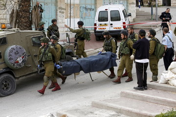 Israeli soldiers carry the dead body of one of two Palestinians, whom the Israeli military said were shot dead by Israeli troops after they attacked an Israeli soldier, in Tal Rumaida in the West Bank city of Hebron