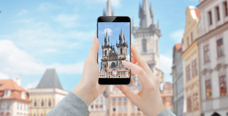 Girl using smartphone to take photo of old cathedral in Prague