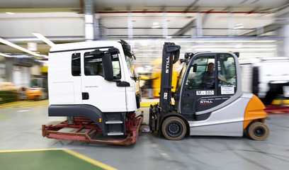 A worker moves a driver cabin in the truck production plant of German truck and bus-maker MAN AG in Munich