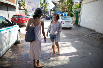 French tourist Camelis, who was injured while fleeing with others after a gunman opened fire during a BPM electronic music festival at the Blue Parrot nightclub, talks to a woman in Playa del Carmen
