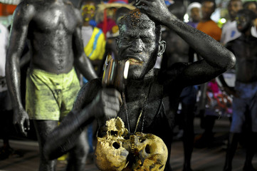 A Carnaval goer eats glass during Carnaval in Haiti's third largest city, Les Cayes