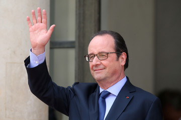 French President Francois Hollande waves outside the Elysee Palace in Paris, France