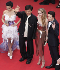Actor Chan waves as he arrives on the red carpet with unidentified guests for the screening of the film De rouille et d'os at the 65th Cannes Film Festival