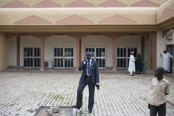 A crier in the royal court poses for a photograph in the courtyard of the emir's palace in Kano