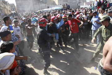 Firefighters carry the body of a victim after a building collapsed in downtown Casablanca
