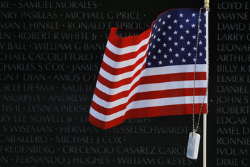 US flag with military dog tag is shown at Vietnam Veterans Memorial  in Washington
