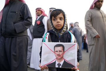 A boy holds a crossed out image of Syria's President Bashar al-Assad during a protest against Russia's role in Aleppo, across the street from the Russian Embassy compound in Shaab