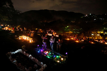 """People light candles, next to a grave in the cemetery """"Jardines de la Aurora"""", to mark the beginning of the Christmas festivities, in Cali"""