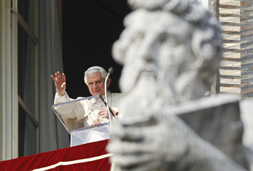Pope Benedict XVI waves as he leads the Sunday Angelus prayer from the window of his private apartment at the Vatican
