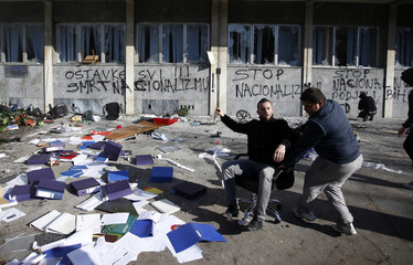Protesters play near scattered documents taken from a government building in Tuzla