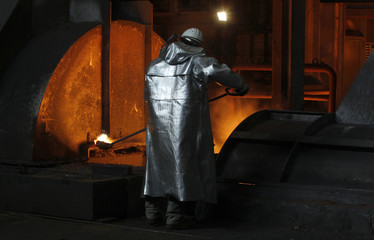 A worker of German steelmaker ThyssenKrupp takes a sample of boiling metal from a blast furnace in Duisburg