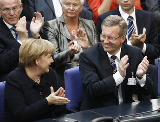 German Chancellor Merkel and presidential candidate Wulff, Lower Saxony federal state Prime Minister of the Christian Democratic Union party CDU, applaud during the presidential election in the Reichstag in Berlin