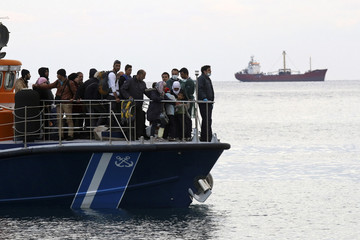 A coast guard vessel carries migrants evacuated from the Kiribati-flagged MV Baris cargo ship seen in the background near Ierapetra on the island of Crete
