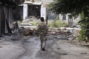 A Free Syrian Army fighter walks along a damaged street in Aleppo