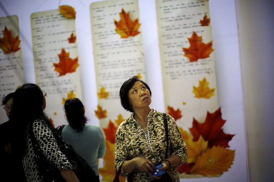 A woman looks at signs showing the personal profiles of people looking for spouses during a matchmaking event for middle-aged singles and seniors in Shanghai