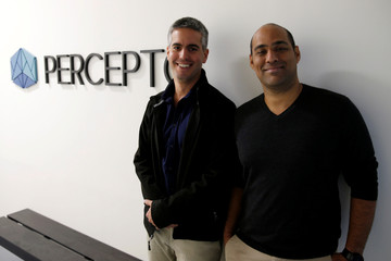 Ariel Avitan (R), Chief Commercial Officer, and Dor Abuhasira, CEO and co-founder of Israeli company Percepto, pose for a photograph next to the company logo at their offices in Modiin, Israel