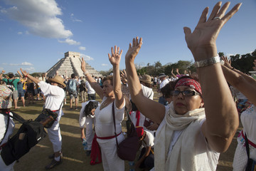 People raise theirs hands at the archaeological site of Chichen Itza in the southern Mexican state of Yucatan