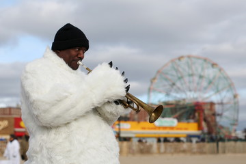 A man in a polar bear costume plays a trumpet before the Coney Island Polar Bear Club's annual New Year's Day swim at Coney Island in the Brooklyn borough of New York.