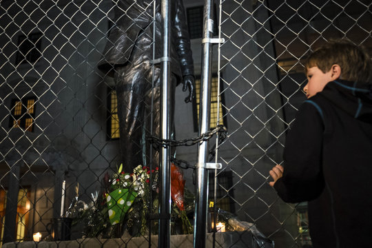 Klein of Bethesda, Maryland, grasps the fence in front of a statue of Nelson Mandela outside the Embassy of South Africa after police locked it with a chain in Washington