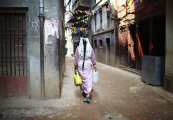 A woman heads back to her home after filling water from a stone spout at Patan, in Lalitpur