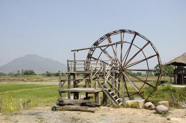 Big wooden turbine baler water wheel at Thai Dam Cultural Village in Chiang Khan at Loei, Thailand