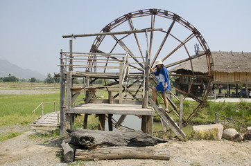 Thai women people travel and posing with big wooden turbine baler water wheel