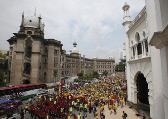 People march past the Malaysian Railway building towards Stadium Merdeka for the opposition People's Uprising Rally in Kuala Lumpur