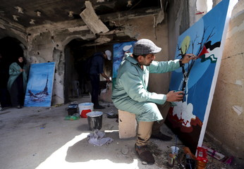 Palestinian artist paints an artwork to be placed on the remains of a house that witnesses said was destroyed by Israeli shelling during a 50- day-war last summer, in Khan Younis in the southern Gaza Strip