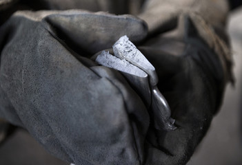 Worker holds a test sample of iron at an iron foundry in Bobruisk