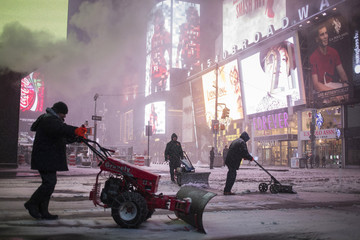 Workers clear the sidewalks during a snowstorm in Times Square, New York