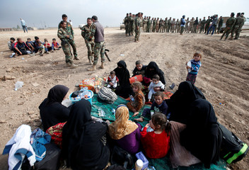Displaced Iraqi women and children sit near Kurdish Peshmerga fighters after escaping from the Islamic State-controlled village of Abu Jarboa