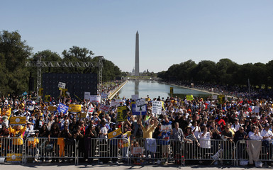 People shout slogans in front of the Reflecting Pool near the Washington Monument at the One Nation Working Together rally in Washington