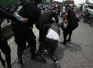 Anti-riot police arrest a protester during a demonstration in Guatemala City